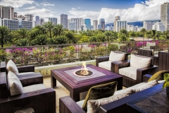 A lounge area on a deck with the city architecture in Honolulu, Hawaii